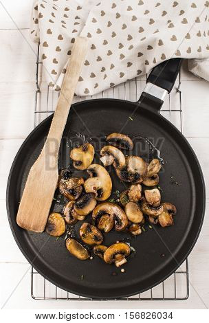 fried mushroom with thyme peppercorn and wooden spatula on a pan
