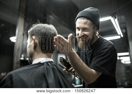 Happy barber with a beard looks at the hair of his client in the barbershop. He holds a cutting comb and a hair clipper. Hairdresser wears a black T-shirt and a cap. Horizontal.