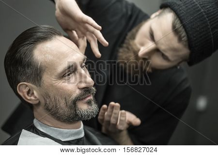 Joyful man with a beard in the barbershop. Bearded barber in a black T-shirt and a cap applies a shaving gel on client's skin. Closeup. Horizontal.