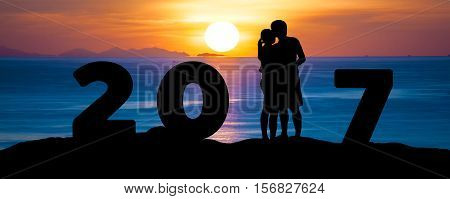 Silhouette of romantic a couple hug kissing against summer sea beach in sunset twilight sky while celebrating happy new year 2017