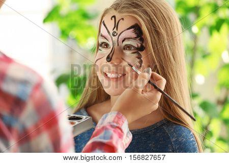 Master making aqua makeup on girls face