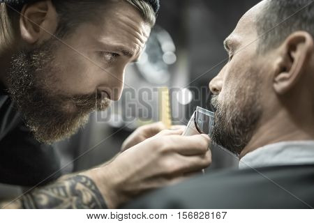 Gifted bearded barber is trimming the beard of his client in a black cutting hair cape in the barbershop. He is using a cutting comb and a hair clipper. Customer sits with closed eyes. Closeup.