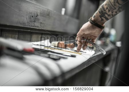 Guy's hand with a tattoo and a straight blade on the blurry background. Finger touches scissors which lie on a white towel on a dark wooden rack with other hairdresser accessories. Closeup photo.