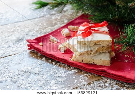 Turron typical Christmas sweet in Spain. Almond nougat on red napkin on dark wooden background with snow and fir tree.
