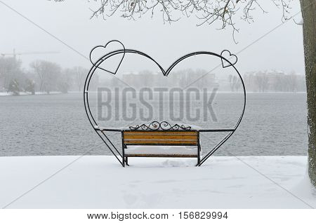 Empty Snow-covered Wrought-iron Bench In The Form Of Hearts For Couple Of Lovers In Winter Park.