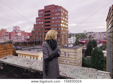 Businesswoman Standing On An Edge Of A Skyscraper's Rooftop