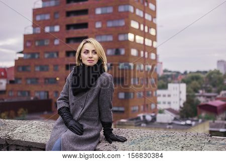 Young Beautiful Woman In Coat And Scarf In Front Of Skyscaper