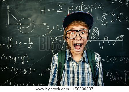 Education, high school, college. Portrait of a funny shouting student boy standing by a school blackboard.