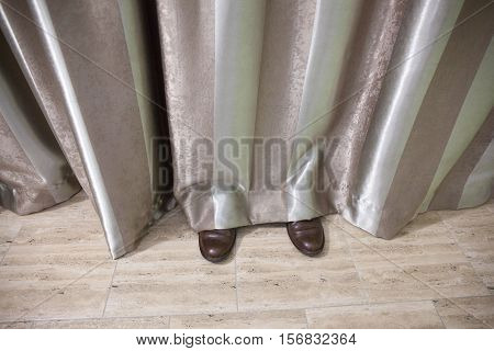 Shoes of a man hidden behind striped curtains in a room.