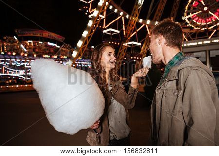 Cheerful young couple eating cotton candy in amusement park