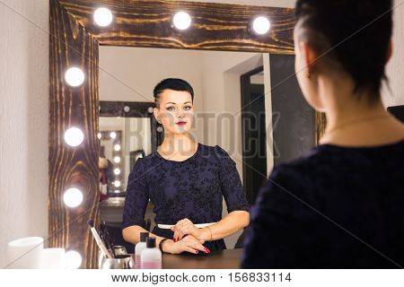 beautiful girl looking through the mirror in dressing room