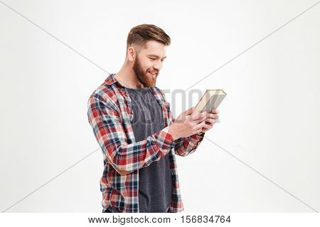 Happy smiling man in plaid shirt looking at the book cover over white background