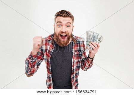 Cheerful bearded man in plaid shirt holding dollar bills over white background