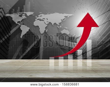 Red arrow with graph on wooden table over black and white world map with financial graph and city tower Success business concept Elements of this image furnished by NASA