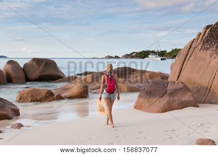 Woman wearing smal backpack, scarf, jeans shorts and beach hat, enjoying view of Anse Lazio beach on Praslin Island, Seychelles. Summer vacations on picture perfect tropical beach concept.