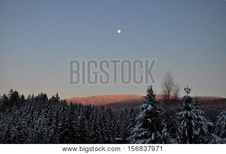 Colorful and crisp image of moonrise in winter scenery