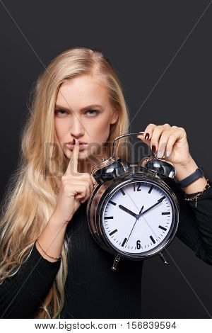 Serious woman holding alarm clock and holding finger on lips, over grey background