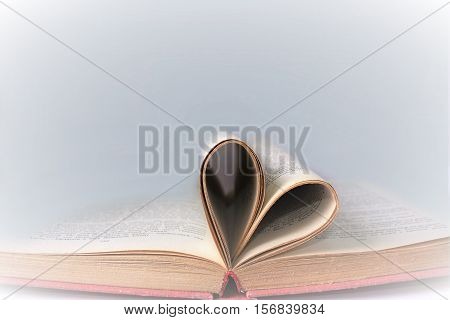 Heart shaped book pages. Old book page decorate to heart shape. Composition of love with open book rolled in heart.