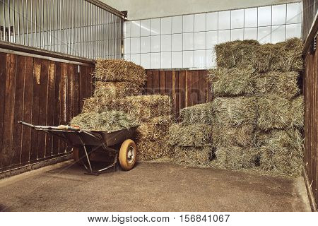 Dry hay stacks in rural wooden barn interior with a wheelbarrow
