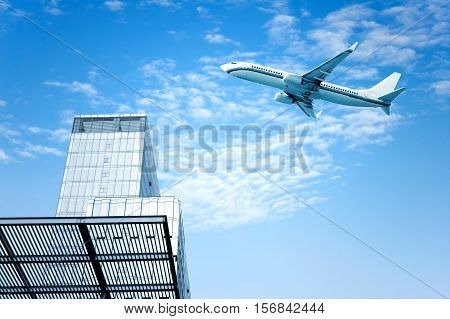 High-rise next to a passenger plane flew across the sky.