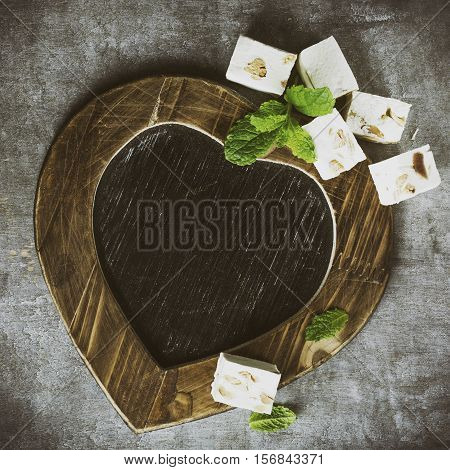 Valentines Day background with vintage slate chalk board in heart form and soft nougat blocks with peanuts and fruit with copy space for text. Retro style toned. View from above.