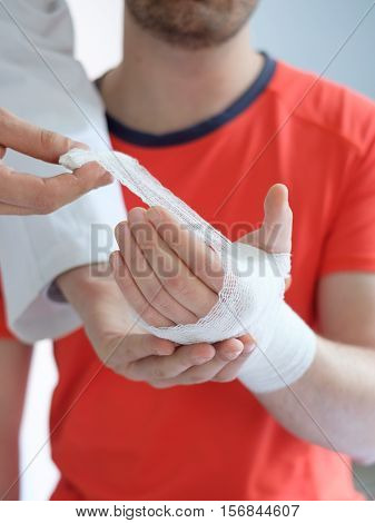 Doctor Bandaging The Hand Of A Sport Man After An Accident