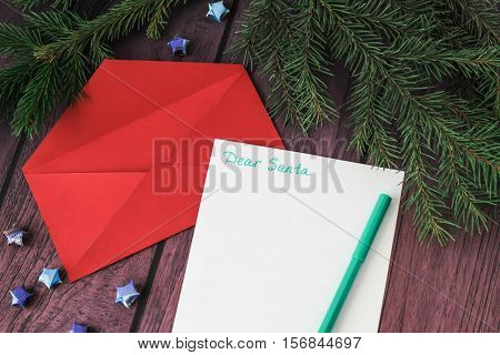 Empty letter red envelope and a pen on a wooden background with christmas decoration candy canes christmas tree