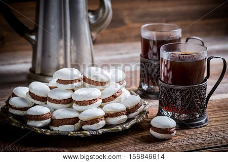 Chocolate Macaroons Served With Coffee On Old Wooden Table