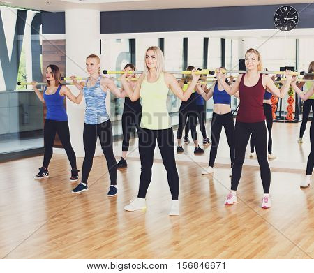 Squats with weights on training. Group of young women in aerobics class making exercises. Girls get ready for squats with barbells. Healthy lifestyle in fitness club