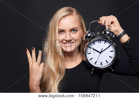 Hand counting - number three. Smiling woman holding big alarm clock showing three fingers, portrait over grey background