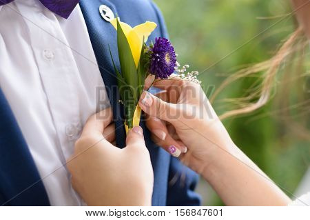 groom boutonniere helps to put her fiance