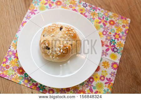 tea cake rasin bun with sugar on it on a plate on a flower napkin on wooden table