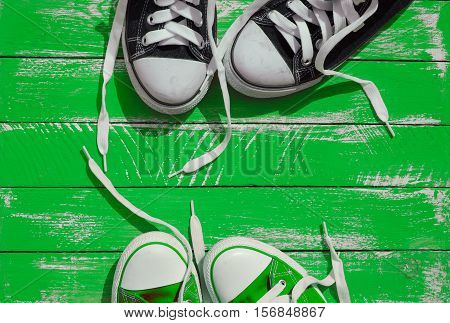 Two pairs of sneakers youth with untied laces on the green wooden surface top view
