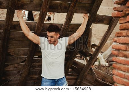 Attractive guy with white t-shirt in a old house. Image for ad