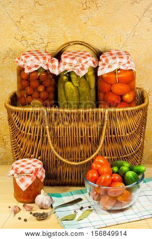 Homemade Canned Vegetables (Tomatoes Cherry Cucumbers Tomatoes) In Glass Jar On Wicker Basket Fresh Vegetables (Tomato Cucumbers) In Glass Bowl Garlic Bay Leaf Metal Spoon With Allspice Tomato Sauce On Wooden Table.