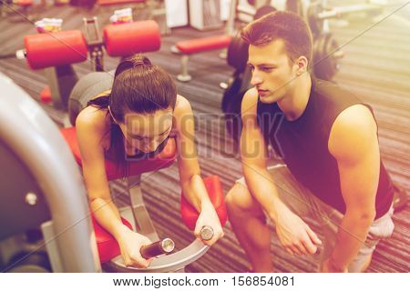 sport, fitness, lifestyle and people concept - young woman and personal trainer flexing leg muscles on gym machine poster