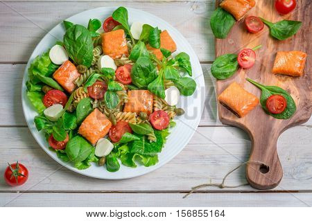 Salad With Salmon And Fresh Vegetables On Old Wooden Table