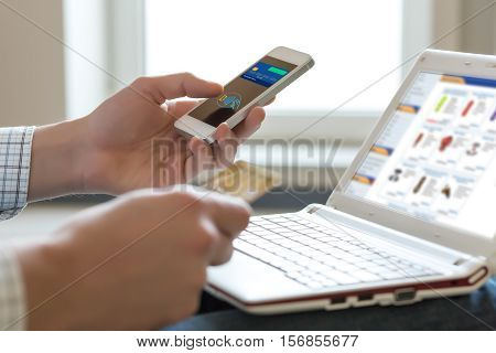 Hands of Person shopping in Internet making instant Mobile Telephone Payment Transaction