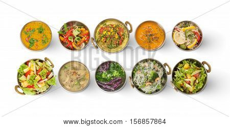 Vegan or vegetarian restaurant dishes top view, hot spicy indian soups, rice and salads in copper bowls. Traditional indian cuisine meal assortment isolated on white background. Healthy eastern food