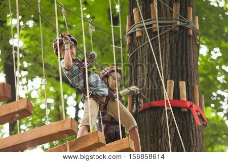 A boy in a helmet and safety equipment in adventure ropes park on the background of nature