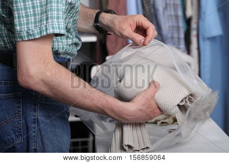 Man packing his clothes in the vacuum pack