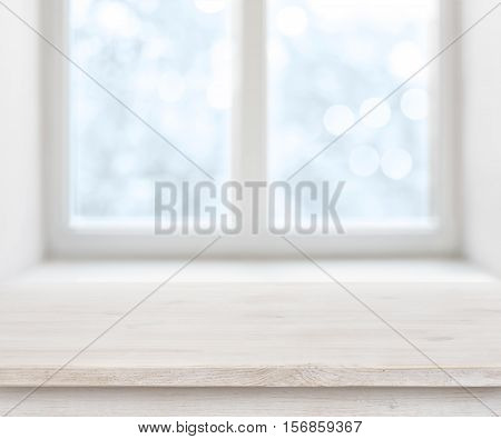 Wooden texture table surface over abstract frosty winter window background