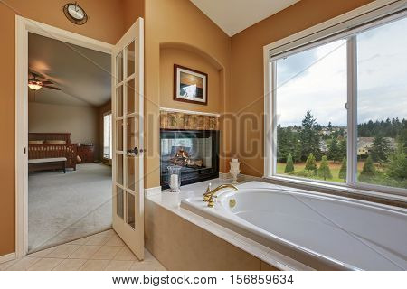 Luxury Bathroom Interior. Wall Mounted Fireplace With Bath Tub