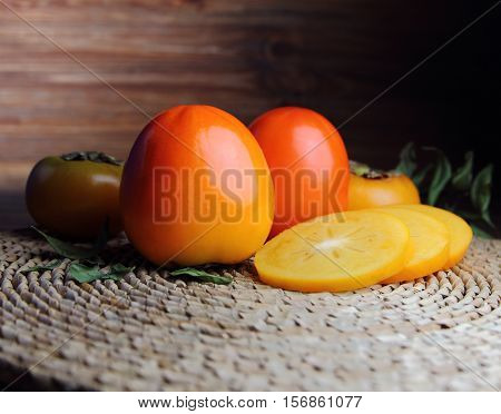 fresh persimmon and persimmon slices on a straw napkin with leaves