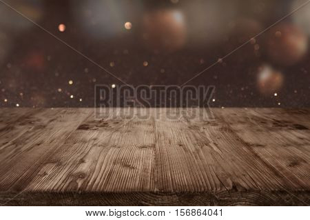 Festive background with shimmering light and bokeh in front of a wooden table