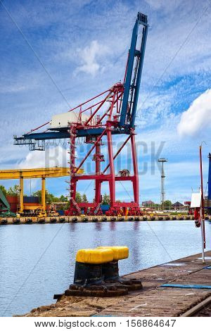Gantry cranes in a harbor on a background of the blue sky.
