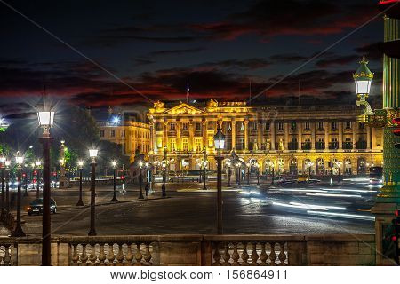 Many street lamps illuminate the Place de la Concorde at night in Paris.