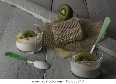 Two glasses with greek yogurt with kiwi and honey with a piece of bee panel and half a kiwi on a wooden board.