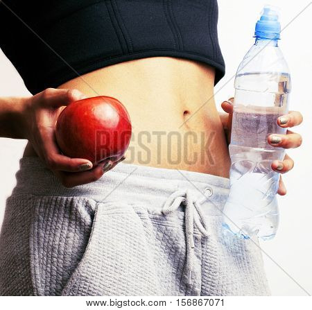 woman measuring waist with red apple and water, african tann isolated close up