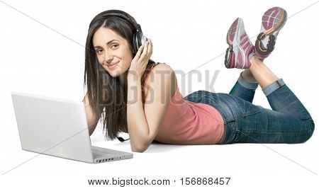 Young woman lying down in front of a laptop wearing headphones